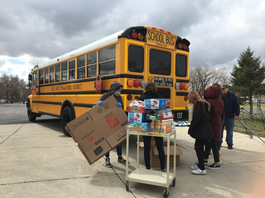 Photo of people standing near a school bus and a cart holding packaged food.