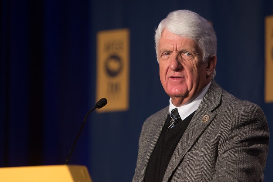 A man with white hair wearing a sweater and a suit jacket stands at a podium.