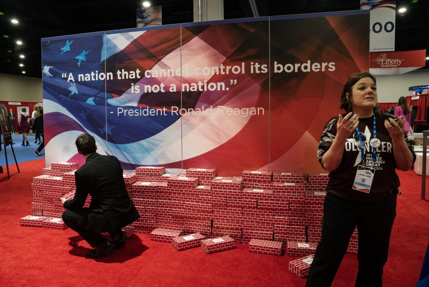 "A fake wall, made of cardboard bricks, is on display with a quote by former President Ronald Reagan that reads: ""A nation that cannot control its borders is not a nation."""