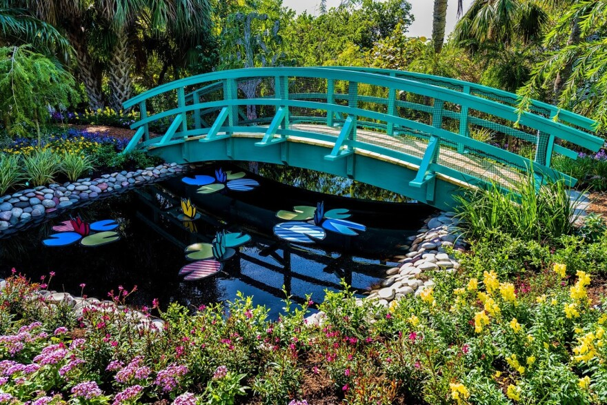 A green footbridge over a pond with 2D water lilies next to a garden.