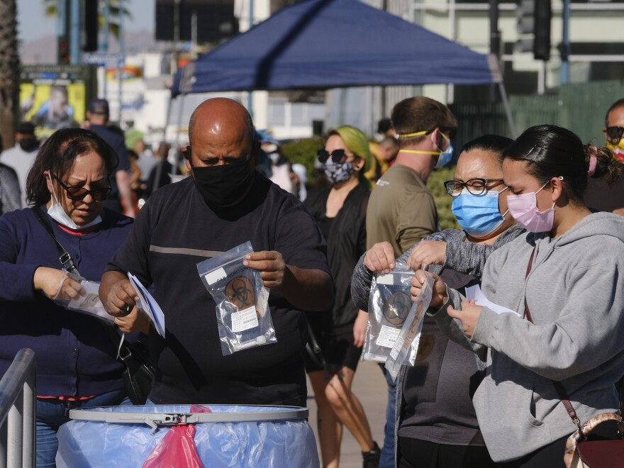 People drop their test kits into an intake receptacle at a COVID-19 testing site in the North Hollywood section of Los Angeles on Saturday. With coronavirus cases surging at a record pace, Gov. Gavin Newsom has warned the state's hospitals could soon be overwhelmed.