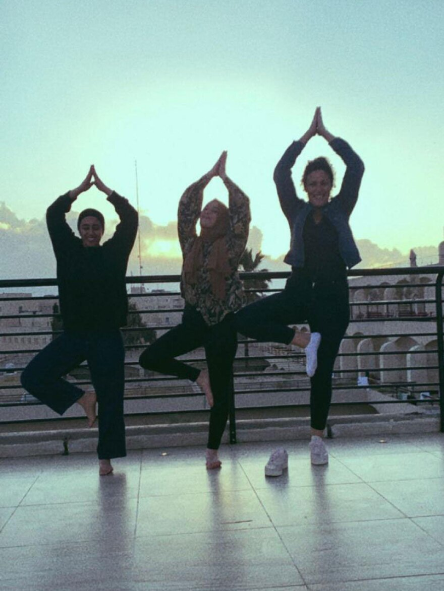 Aysha Abu Shhab (left), Noam Shuster-Eliassi (right) and another patient doing yoga on the hotel terrace.