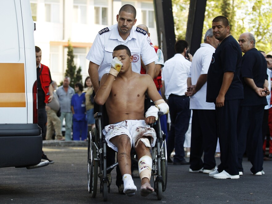 An Israeli survivor is carried on a wheelchair to an ambulance as he leaves a hospital in Burgas, Bulgaria, on Thursday. A suicide bomb attacker killed eight people in a bus transporting Israeli tourists at a Bulgarian airport, the country's interior minister said, and Israel pointed its finger at Iranian-backed Hezbollah militants.