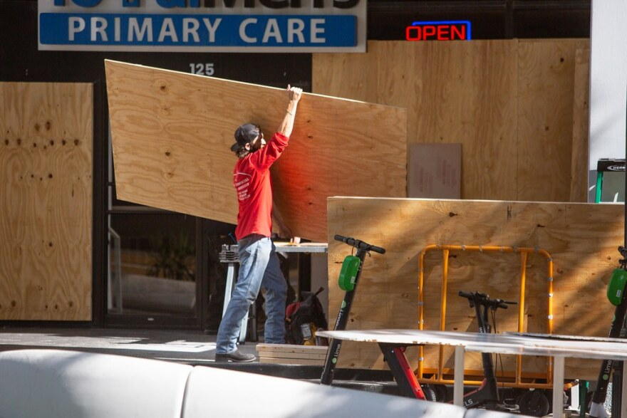 A worker boards up windows in downtown Austin on Monday as a precaution against unrest following the election.