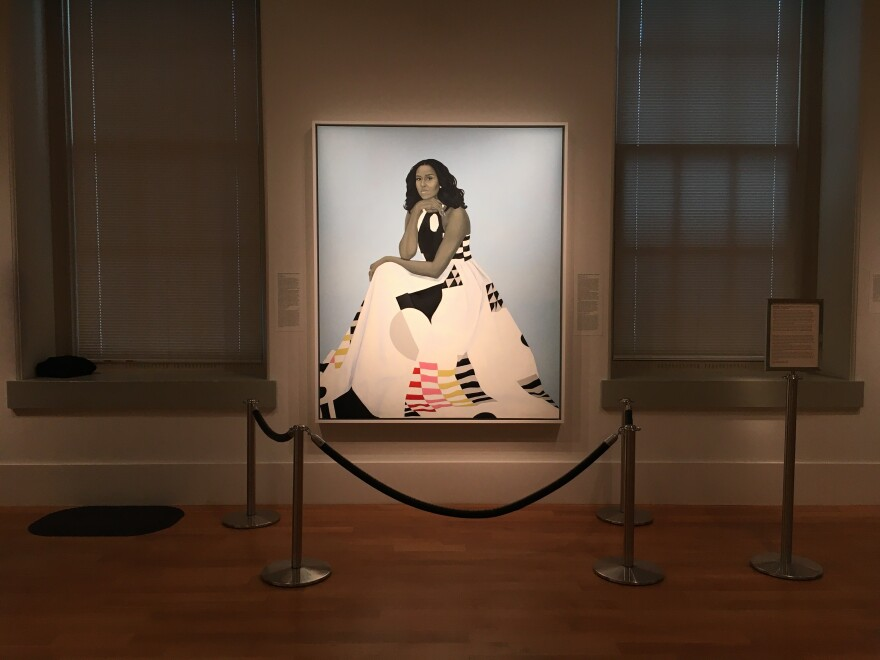 Amy Sherald's painting of Michelle Obama is displayed behind its own ropes.