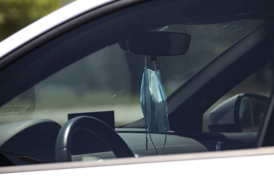 A face mask hangs in the rearview mirror of a car.