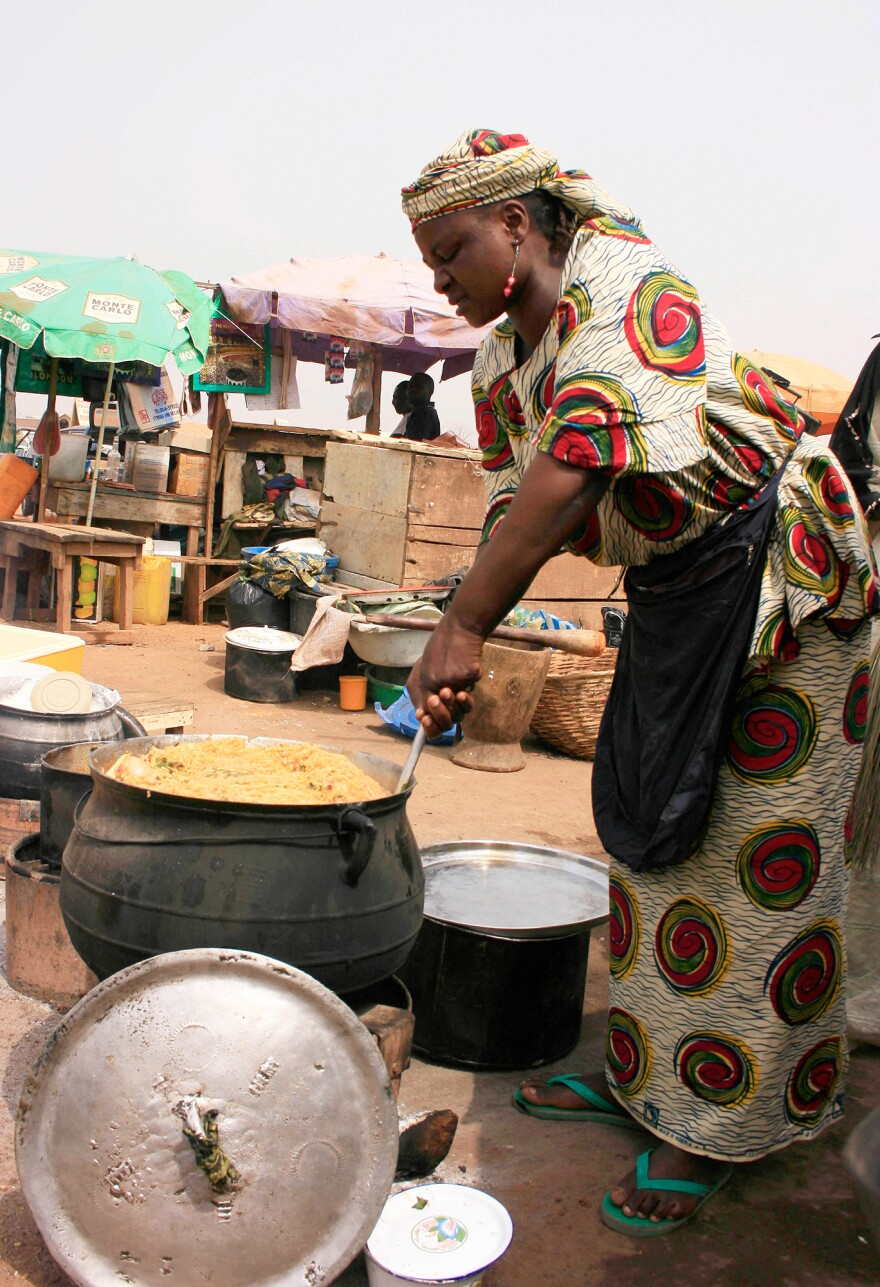 """A food vendor in Kano, Nigeria, prepares jollof rice outdoors in an iron pot. When it comes to jollof, my Nigerian friend Ronke Onadeko argues, """"the taste of perfection is smoke-flavoured."""""""