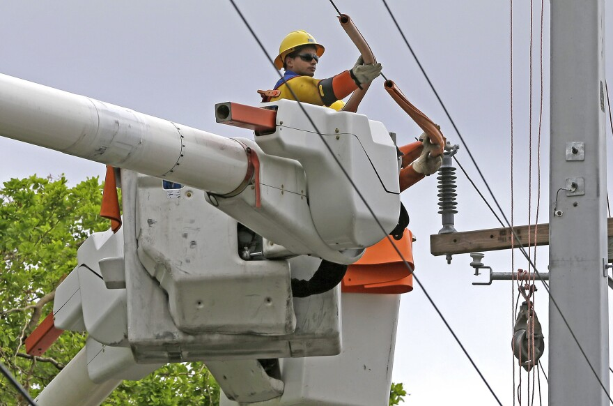 In this Monday, Oct. 2, 2017, photo, a Pike utility worker works on a power line in Miami. On Wednesday, Jan. 17, 2018, the Federal Reserve said U.S. industrial production rose 0.9 percent in December, pulled higher by a surge in utility output, another sign of health for the American economy.