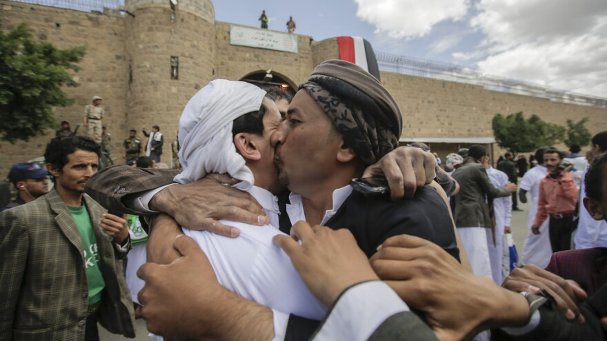 A Yemeni detainee (left) is greeted by a family member after being released by Houthi rebels on Monday. The release was brokered by the International Committee of the Red Cross.