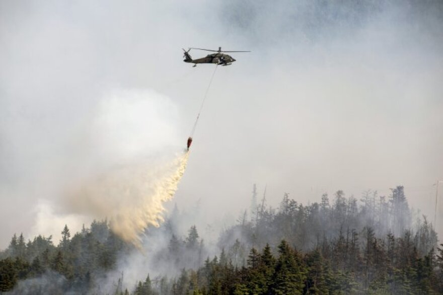 """Alaska Army National Guard UH-60 Black Hawk helicopter from 1st Battalion, 207th Aviation Regiment drops approximately 700 gallons of water from a """"Bambi Bucket"""" on to the Stetson Creek Fire near Cooper Landing, Alaska, June 17"""