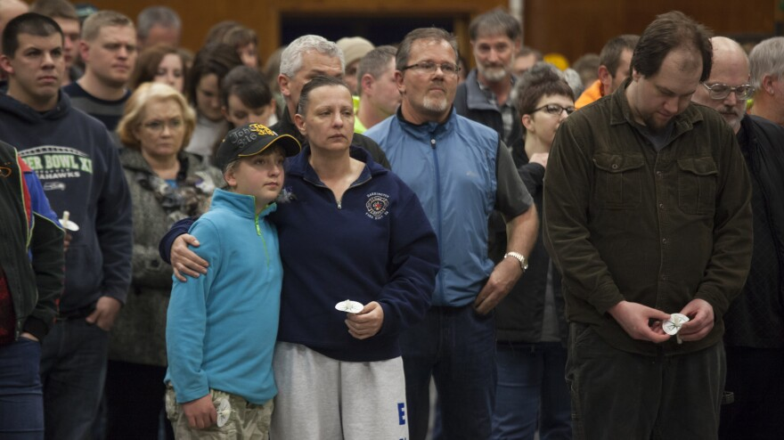 Gabriella Botamanenko (center left) hugs her mother, Angela Botamanenko, during a vigil for mudslide victims at the Darrington Community Center Saturday. A March 22 mudslide in a nearby community killed at least 30 and left many missing.