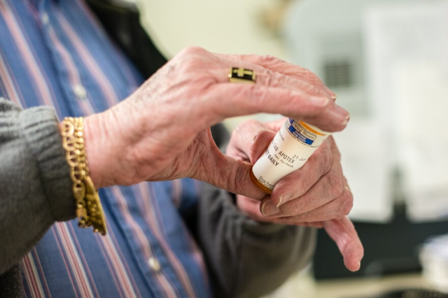 Elderly patient holds prescription pill bottle.