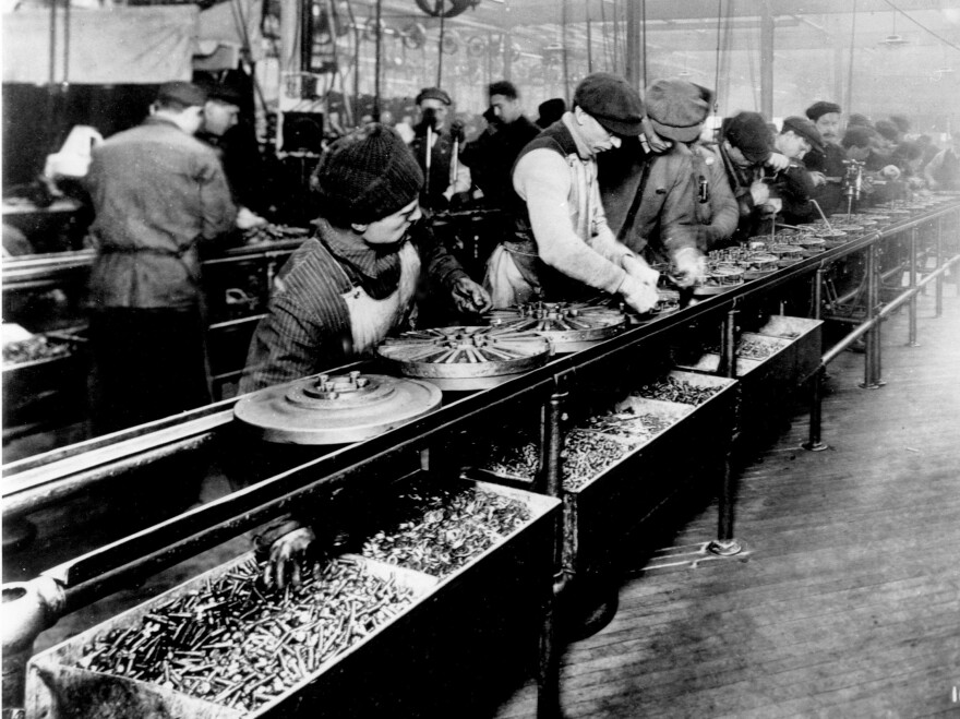 Ford's use of a moving line reduced a car's assembly time from 12 hours to 93 minutes, but this made the work repetitive for workers like the ones here, who are making flywheels. So Ford paid workers $5 a day, an extraordinary amount at the time.