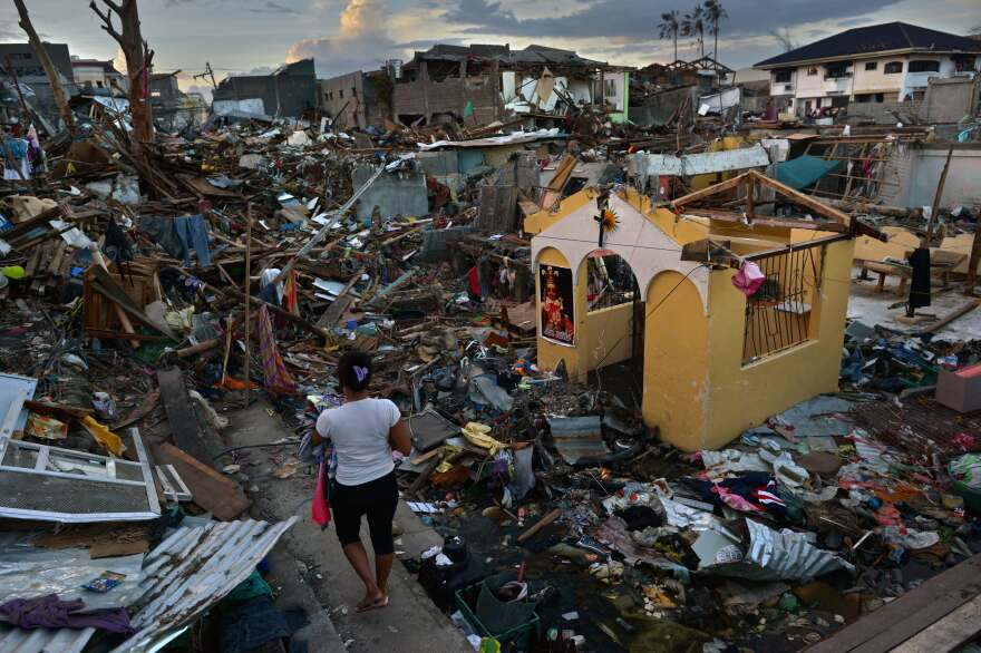 A typhoon victim walks past a destroyed church outside her home in Tacloban last November.