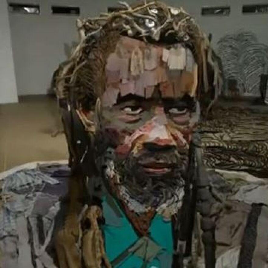 An anamorphic installation portrait of Malian actor Sotigui Kouyate by French artist Bernard Pras.
