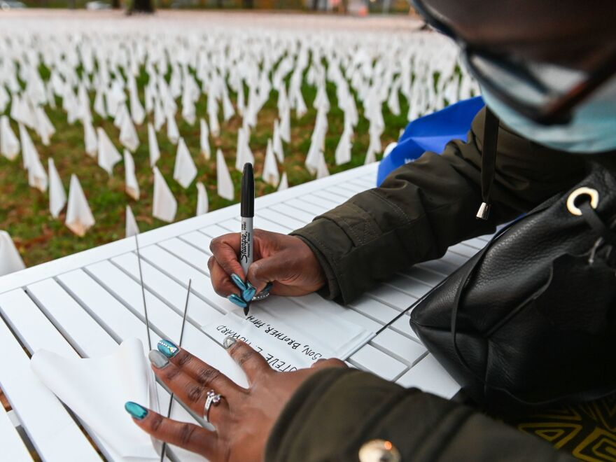 "Patrice Howard writes on white flags before planting them to remember her recently deceased father and close friends in November at ""IN AMERICA How Could This Happen...,"" a public art installation in Washington, D.C. Led by artist Suzanne Firstenberg, volunteers planted white flags in a field to symbolize each life lost to COVID-19 in the U.S."