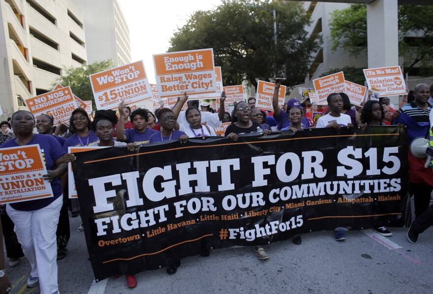 Protestors march in support of raising the minimum wage to $15 an hour as part of an expanding national movement known as Fight for 15, Wednesday, April 15, 2015, in Miami. The event was part of a national protest day to coincide with the April 15 deadlin