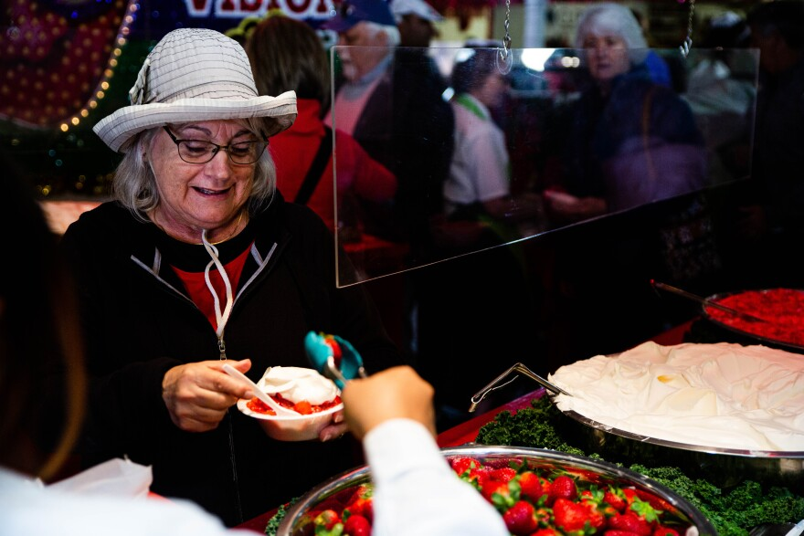 A women is served a strawberry to complete her strawberry shortcake order.