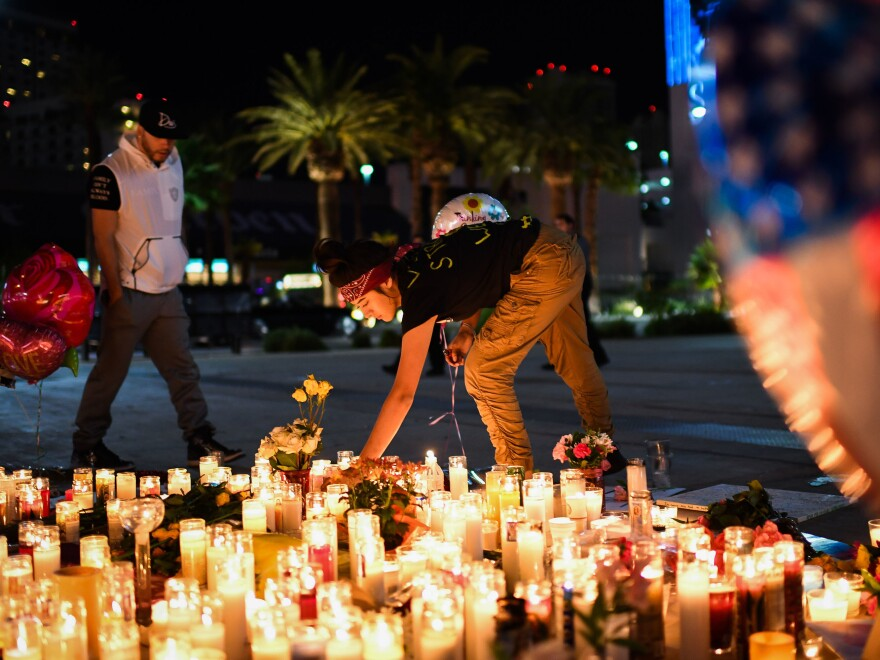 Priscilla Olivas, 19, of Las Vegas lights a candle at a street vigil for shooting victims along the Las Vegas Strip. Olivas was part of the cleaning crew at the concert when a gunman opened fire Sunday.