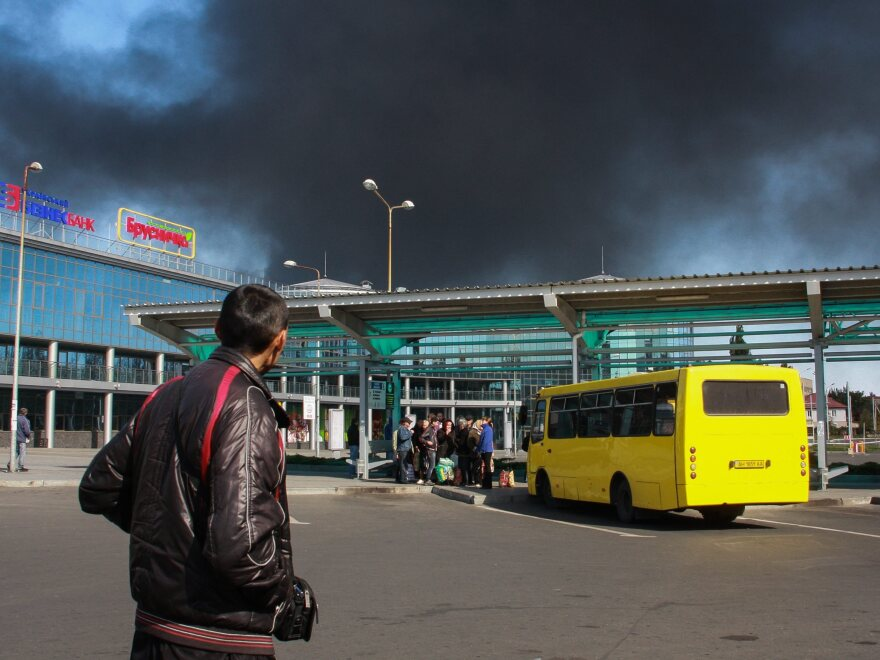 Black smoke from an apparent shelling of the International airport rising into the sky while standing near a railway building, in Donetsk, Ukraine, on Thursday.