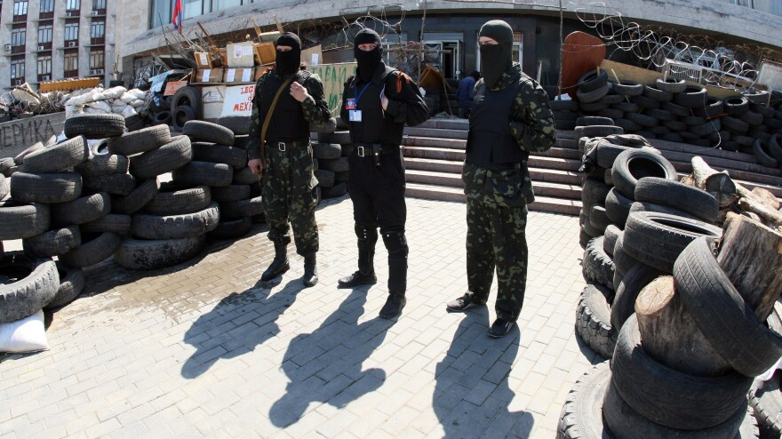 """Masked pro-Russian activists guard a barricade outside the regional state building seized by separatists in the eastern Ukrainian city of Donetsk Saturday. Pro-Russian forces holding a group of international observers have accused them of being """"NATO spies."""""""