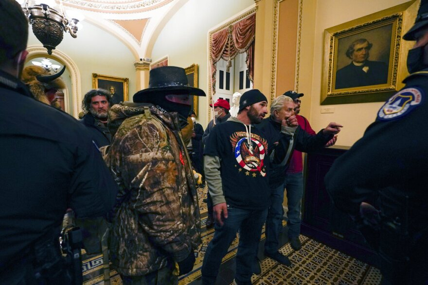 Protesters walk as U.S. Capitol Police officers watch in a hallway near the Senate chamber at the Capitol in Washington on Wednesday.