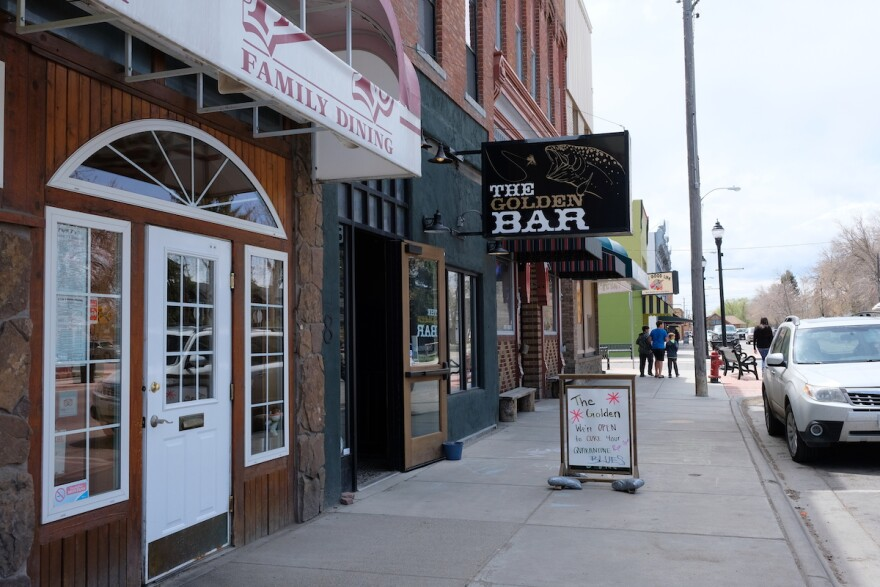 A family walks past restaurants and bars in Dillon, Montana, May 12, 2020.