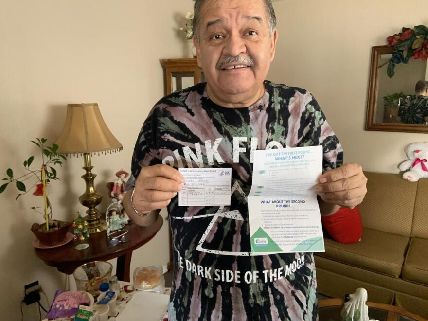 Manuel Mendez shows off his immunization record showing he's received the first dose of the COVID-19 vaccination.