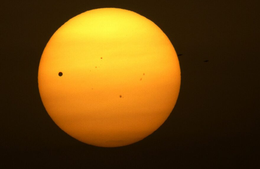 Planet Venus, pictured as a black dot, left, is seen in transit across the sun on the banks of the Ganges River in Varanasi, India, Wednesday, June 6, 2012. (Rajesh Kumar Singh/AP)
