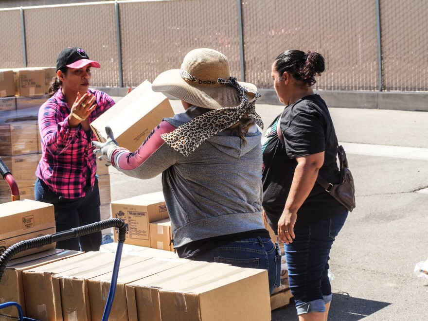 Volunteers and paid staff unload boxes of cheese, bread and rice for needy people in Heber, many of them elderly.