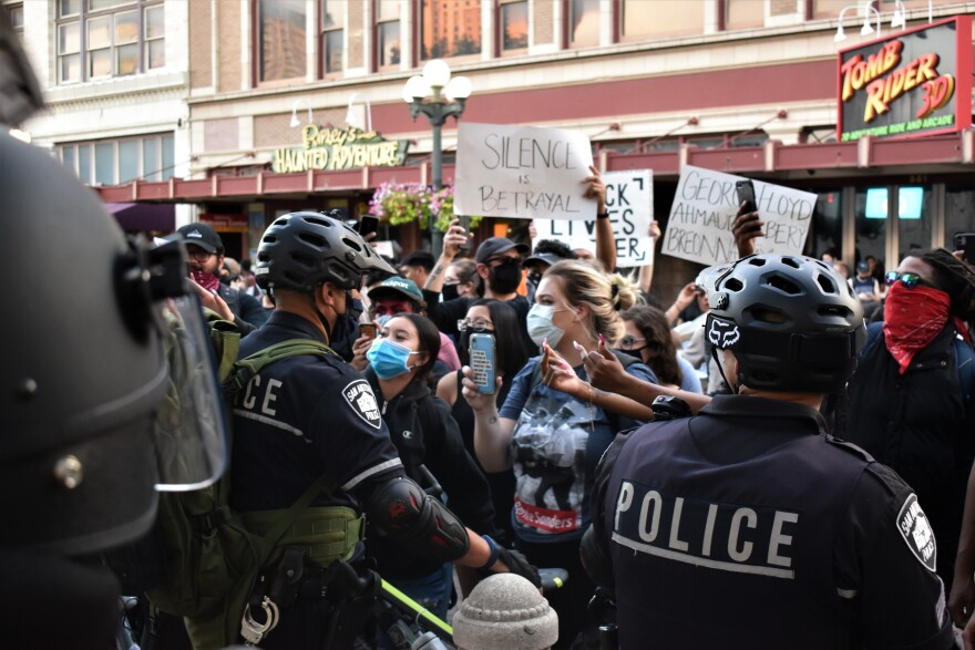 Police officers in riot gear face protestors in downtown San Antonio on Saturday May 30, 2020.