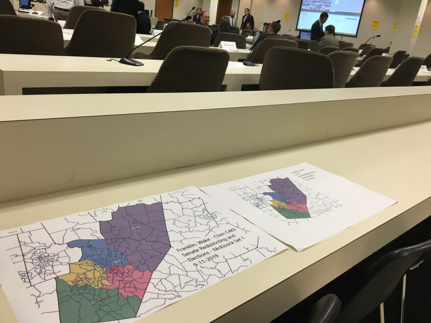 Map printouts showing voting districts in Franklin and Wake counties sit on a table during a North Carolina Senate redistricting committee meeting.
