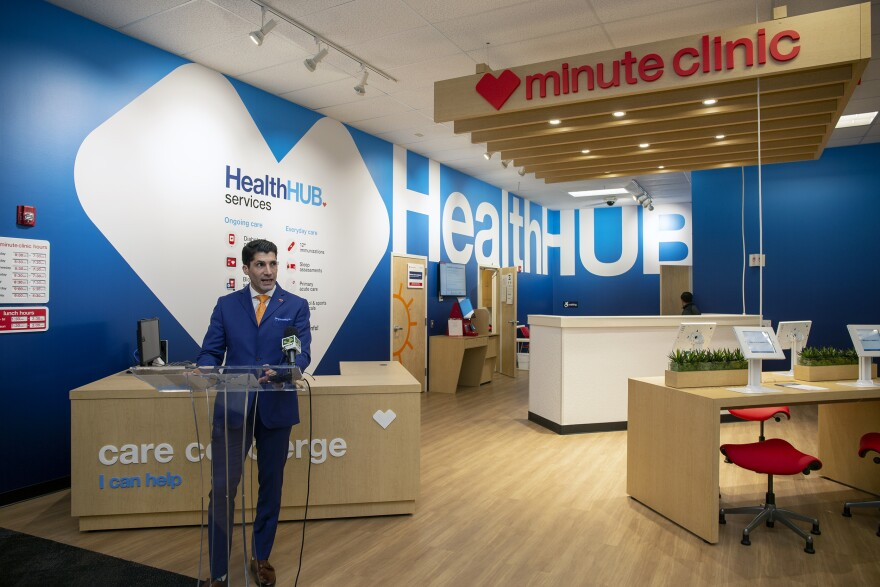 A man in a blue suit stands at a podium in front of a open plan health clinic inside a CVS pharmacy.