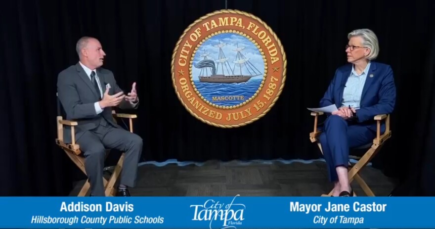 man and woman sit on chairs and speak to each other in front of City of Tampa seal