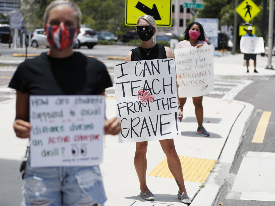 Middle school teacher Brittany Myers (center) stands in protest last week at the Hillsborough County School District Office in Tampa, Fla. Teachers and administrators have rallied against the reopening of Florida schools due to concerns about the coronavirus.