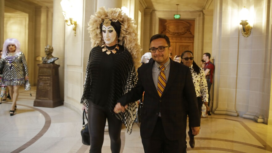 """San Francisco City Supervisor David Campos (right) walks with drag queen Sister Roma to a news conference on Sept. 17 about a Facebook policy that requires people to use their """"real"""" names on their profiles. The site said Wednesday it will modify how the policy is enforced."""