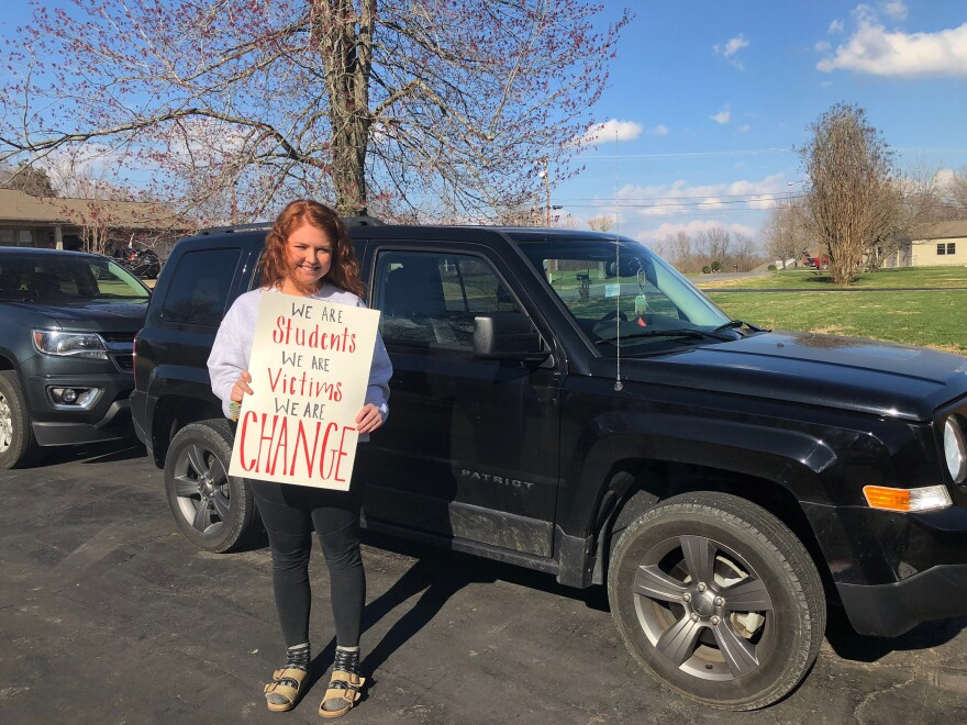 Keaton Conner holds protest signs in front of her jeep. Conner, a junior at Marshall County High School, was heartbroken by her school's shooting. Then she was inspired by the protest movement started by students from Stoneman Douglas.