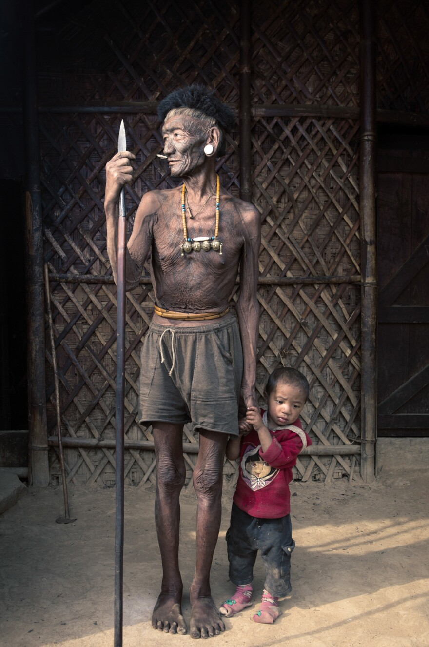 Wanglei Wangshu, 79, with his grandson. His face tattoo indicates that he has participated in a headhunting expedition. But he doesn't have the neck tattoo that's a sign that he decapitated someone.