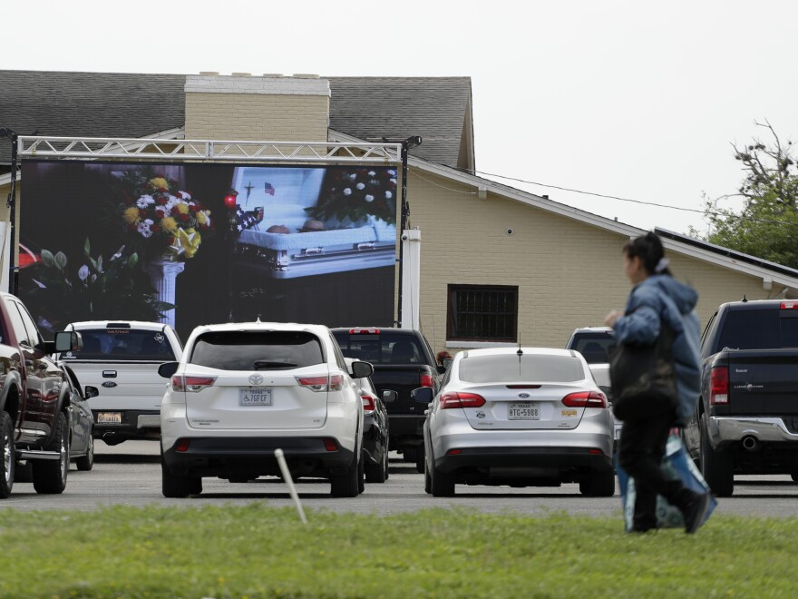 Amid the COVID-19 outbreak, a funeral service is shown on a screen to drive-up attendees in San Antonio on Tuesday. San Antonio is under stay-at-home orders and people are encouraged to observe social distancing.