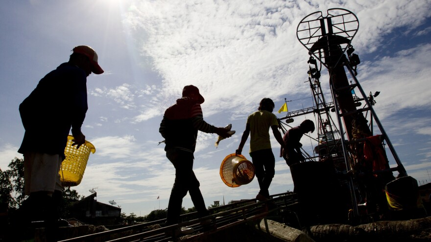 "Migrant workers from Myanmar return to a trawler after unloading fish following a fishing trip in the Gulf of Thailand in Samut Sakhon province Tuesday. A new report details ""deceptive and coercive"" labor practices in the Thai fishing sector, which relies heavily on workers from Cambodia and Myanmar, also known as Burma."