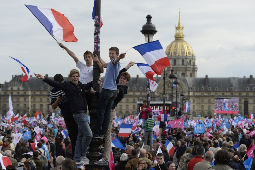 """Thousands of supporters of the anti-gay marriage movement """"La Manif Pour Tous"""" (Demonstration for all) wave flags as they gather at the Invalides square in Paris on Sunday."""