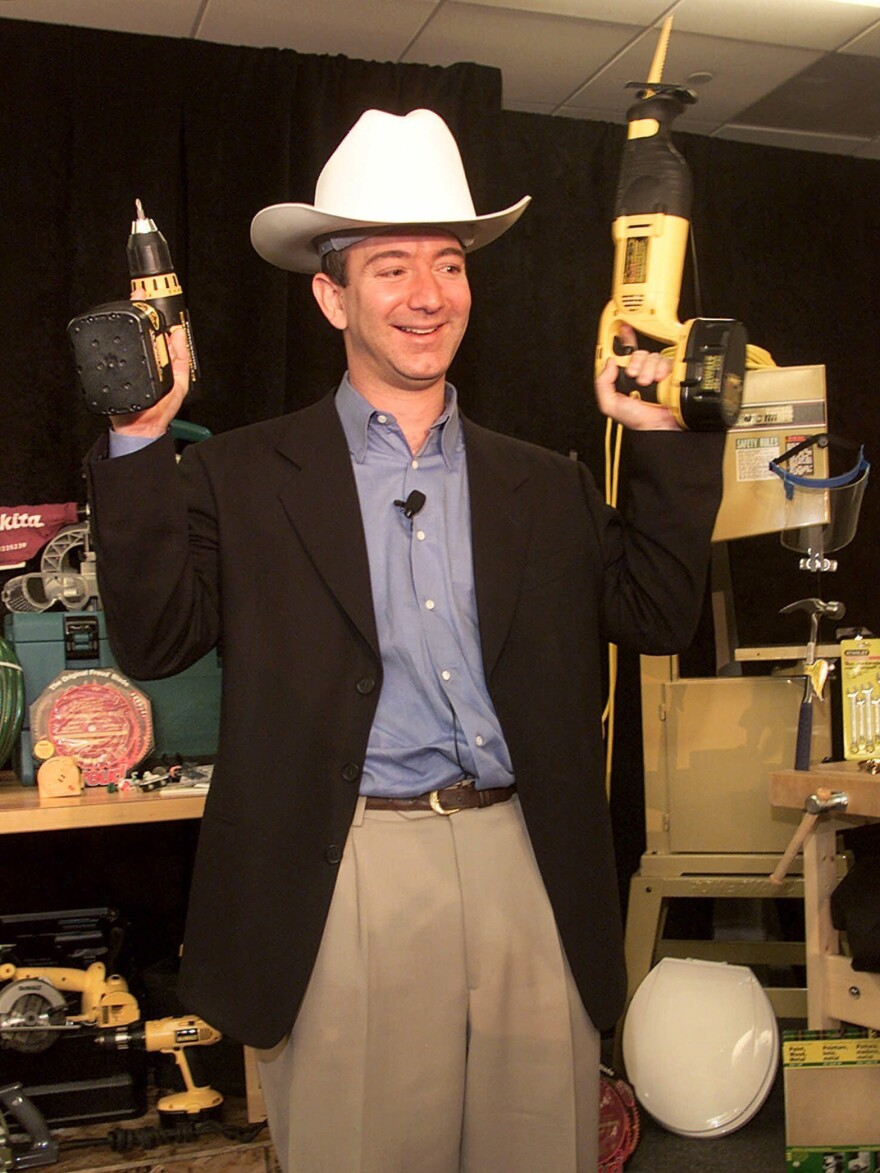 With Amazon expanding its selection, Bezos poses with a power drill and reciprocating saw in a Western-style hard hat at a 1999 news conference in New York.