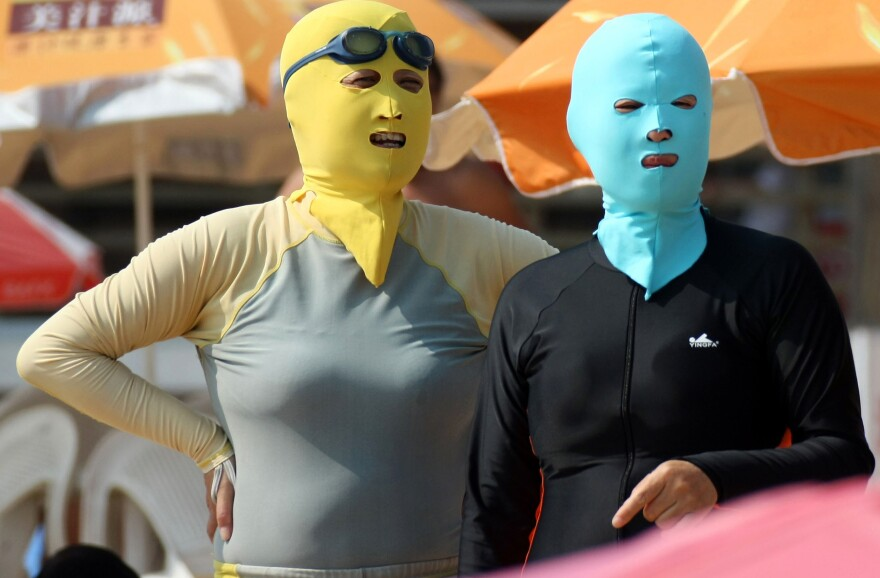 Chinese beachgoers wear face-kinis in Qingdao, northeast China's Shandong province. The face masks allow people to enjoy the water and sand — but not the effects of the sun.