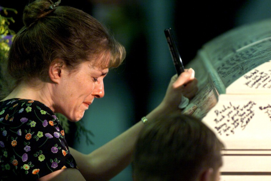 Columbine High School teacher Paula Reed is overcome with grief after signing Rachel Scott's casket during funeral services on April 24, 1999.