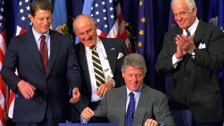 House Minority Leader Bob Michel (center) looks over President Clinton's shoulder as he signs legislation implementing the North American Free Trade Agreement. Vice President Al Gore (left) and House Speaker Thomas Foley also look on.