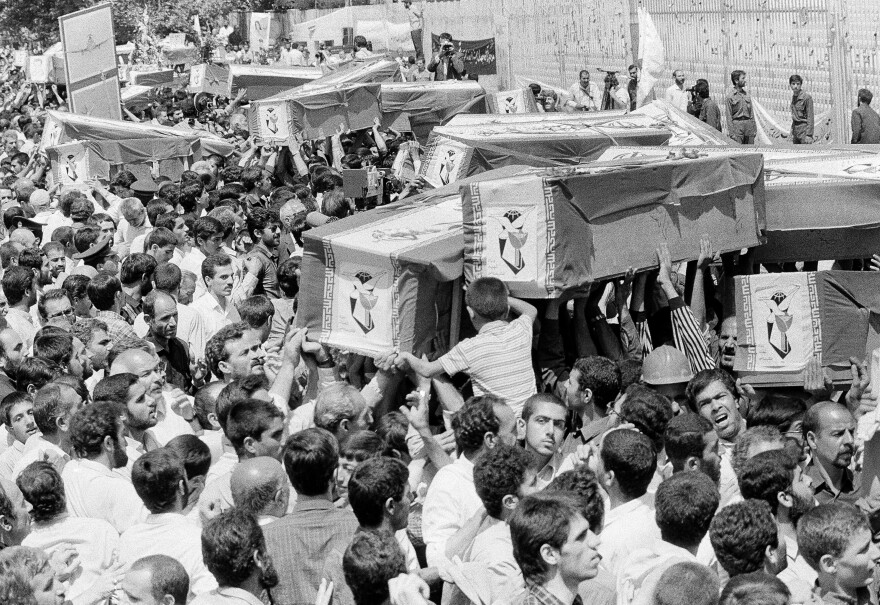 Mourners carry coffins through the streets of Tehran, Iran, on July 7, 1988, during a mass funeral for victims of a downed Iran Air flight. The U.S. Navy shot down the civilian plane in the Persian Gulf, killing all 290 onboard, after mistaking it for an Iranian warplane.