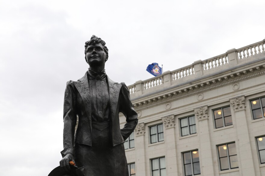 Statue of a 19th century woman standing in front of a government building. The Utah state flag flies in the background.
