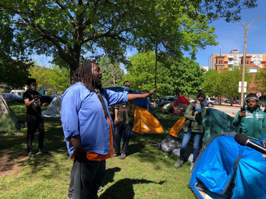 A man at the encampment speaks to police and as onlookers videotape the exchange Friday morning.