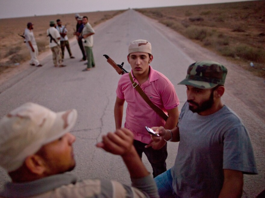 Libyan rebel soldiers stand guard Monday at the last outpost before the desert town of Bani Walid. The town is one of the few places still controlled by Gadhafi supporters, and rebels have been preparing for an assault.