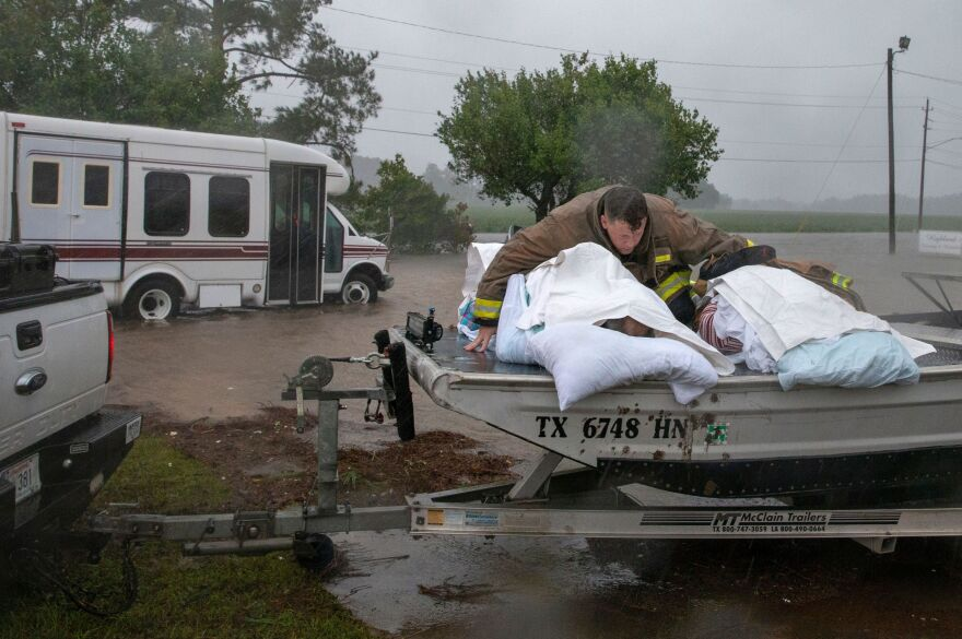 "A Lumberton firefighter on Saturday holds on to two nursing home patients as a member of the ""Cajun Navy"" drives his truck during the evacuation of a nursing home due to rising flood waters in Lumberton, N.C."